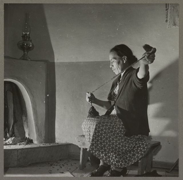 Trampas, New Mexico. Maclovia Lopez, wife of the majordomo (mayor), spinning wool by the light of the fire. The family has ten sheep and they spin the wool for blankets, which are woven for them in Cordova