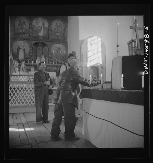 Trampas, New Mexico. Member of the congregation leaving an offering during a memorial mass in church which was built in 1700 and is the best-preserved colonial mission in the Southwest