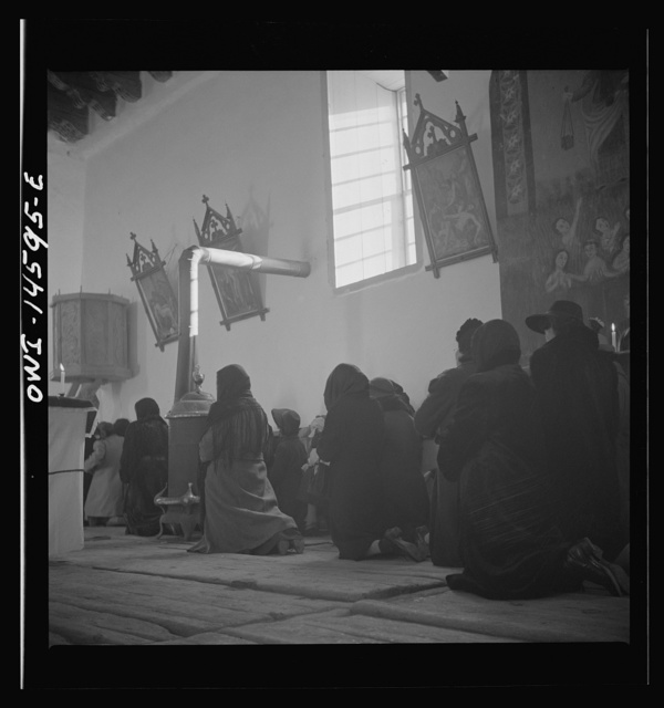 Trampas, New Mexico. Memorial mass at a church which was built in 1700 and is the best-preserved colonial mission in the Southwest. The altar in the center is a symbolic coffin. The congregation during the celebration of a mass