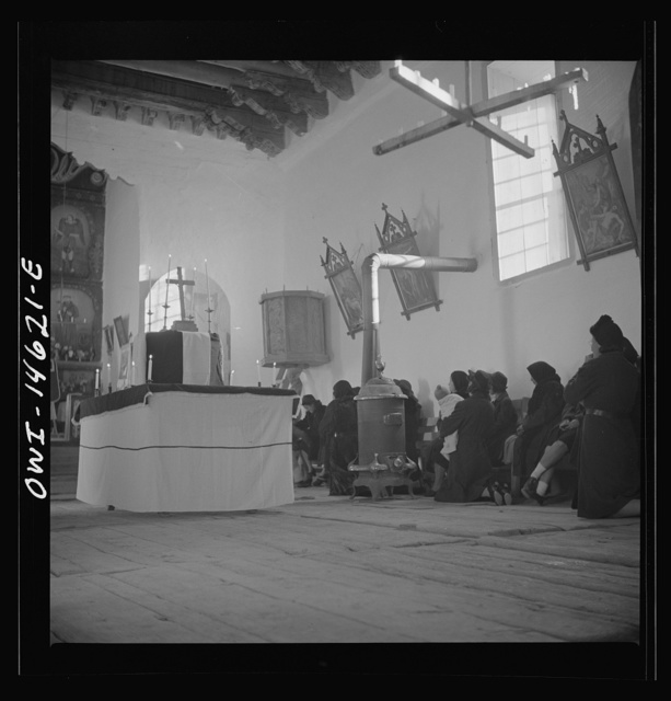Trampas, New Mexico. Memorial mass at a church which was built in 1700 and is the best-preserved colonial mission in the Southwest. Altar in the center is a symbolic coffin