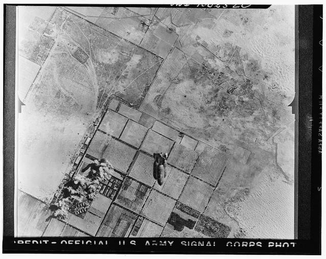 Tripoli, Libya. Allied air forces bombs rain down on Castel Benito airdrome during a daylight raid which damaged machine shops and other installations. In the foreground a train of bombs may be seen dropping from the bay of a United States plane