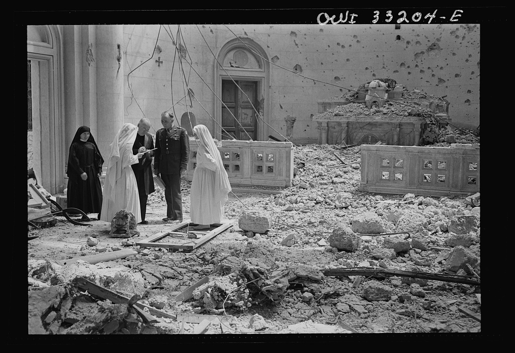 Tripoli, Libya. Archbishop Spellman of New York (left) surveys the ruins of the chapel of the Franciscan Missionaries of Mary. With him are Brigadier General Auby C. Strickland of the U.S. Army 9th Air Force and Catholic nuns