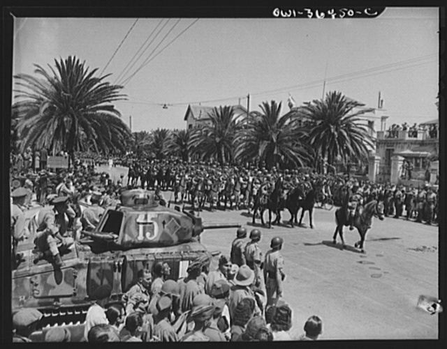 Tunis, Tunisia. Colorful Sphi troops of the French colonial army passing a French tank in the foreground in the Allied victory parade along Avenue Gambetta