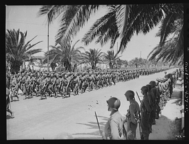 Tunis, Tunisia. French soldiers marching in the Allied parade along Avenue Gambetta. American soldiers standing at parade rest in the foreground