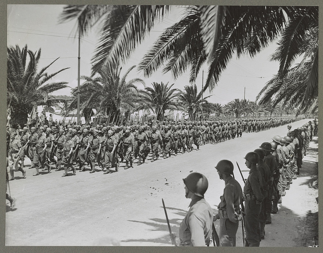 Tunis, Tunisia French soldiers marching in the allied victory parade along Avenue Gambetta. American soldiers standing at parade rest in the foreground.