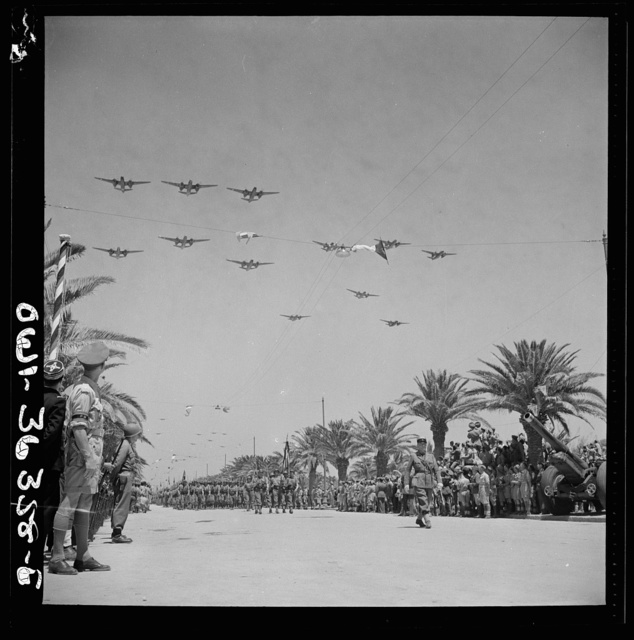 Tunis, Tunisia. French troops passing the reviewing stand in the Allied victory parade along Avenue Gambetta as American planes fly overhead in a show of Allied might