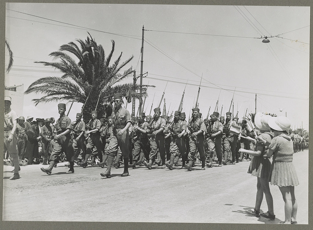 Tunis, Tunisia Two French children waving as French troops march by in the allied victory parade along Avenue Gambetta.
