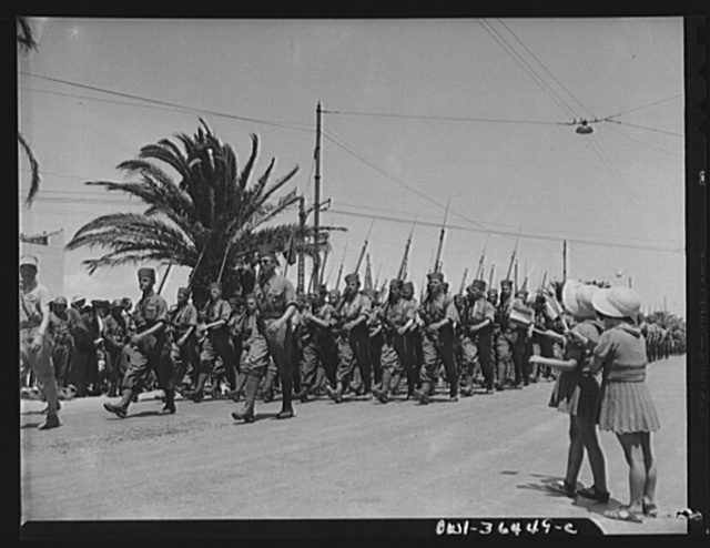 Tunis, Tunisia. Two French children waving as French troops march in the Allied victory parade along Avenue Gambetta