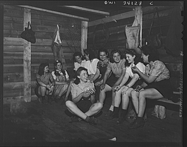 "Turkey Pond, near Concord, New Hampshire. Women workers employed by a U.S. Department of Agriculture timber salvage sawmill. Employees eating their lunch in a shed. In the foreground is Mrs. Daisy Perkins, trimmer. Others, from left to right, Norma Webber, ""pit woman""; Mrs. Violet Storey, ""take-away""; Mrs. Elizabeth Esty and Florence Drouin, ""pond-woman""; Mrs. Dorothy De Greenia, ""slip woman""; Ruth De Roche, ""pit woman""; Barbara Webber, ""edger""; and Mrs. Lucy De Greenia, ""take away"""