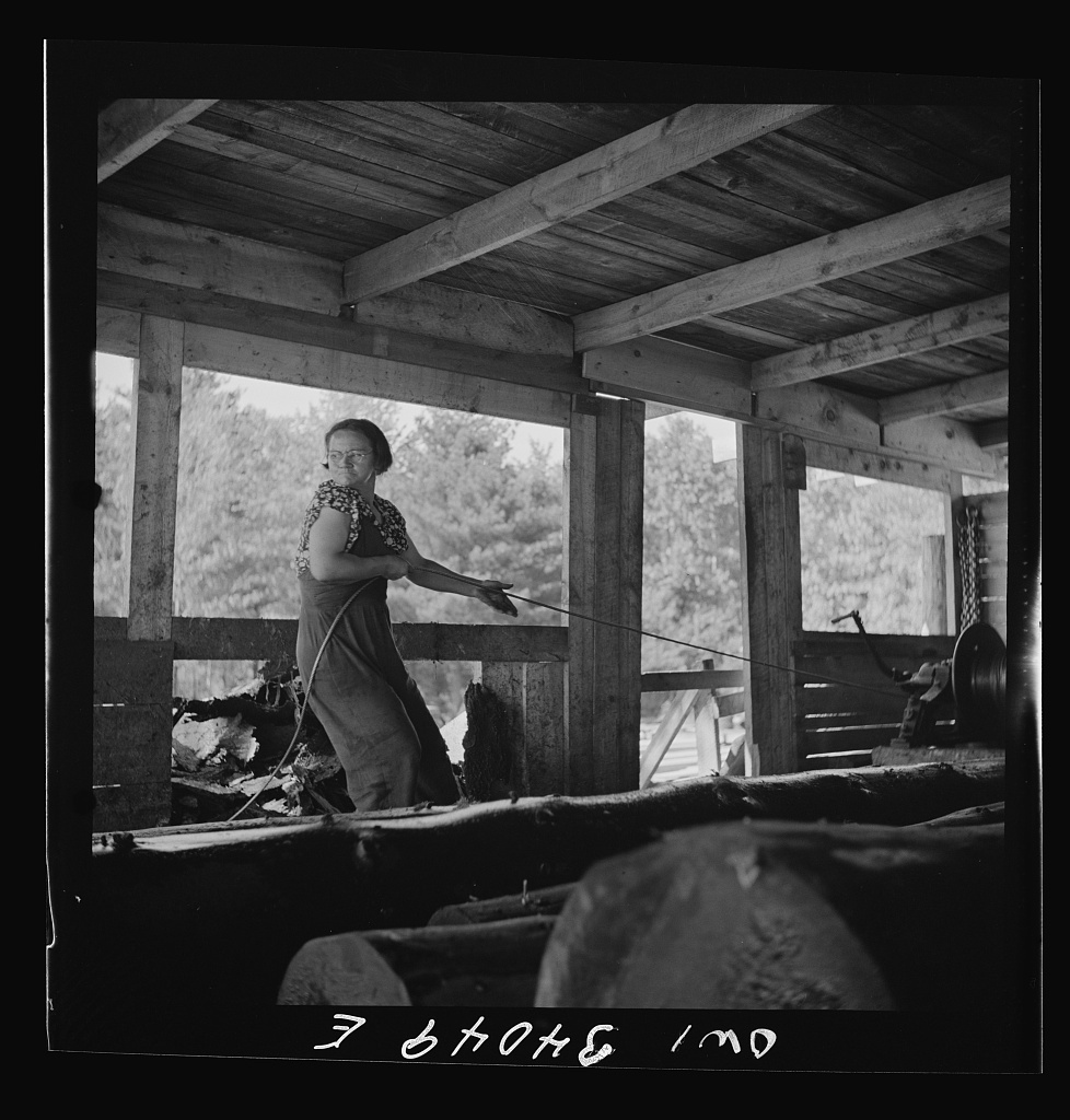 Turkey Pond, near Concord, New Hampshire. Women workers employed by a U.S. Department of Agriculture timber salvage sawmill. Mrs. Dorothy De Greenia, slip woman, pulling out the cable to throw it back down the slip for the next load of logs from the pond