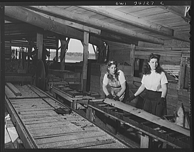 "Turkey Pond, near Concord, New Hampshire. Women workers employed by a U.S. Department of Agriculture timber salvage sawmill. Mrs. Violet Storey, ""take-away,"" and Barbara Webber, ""edger,"" sending a log down the conveyor to be sawed into two-foot lengths for scrap"