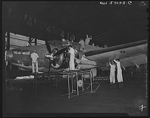 """United States """"lend-lease"""" program in eastern India. A mixed crew of English, Chinese and Indian workmen repair a lend-lease Hudson bomber which was shot up and damaged too badly for field repairs during a bombing raid on the Japanese occupied portion of Akyab, an island off the coast of Burma. The crew named the bomber """"Lulu"""""""