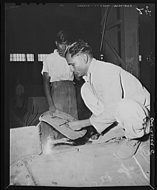 """United States """"lend-lease"""" program in eastern India. An Indian workman, using an American welder which was supplied under lend-lease, welds an armor plate on a nearly completed combat car"""