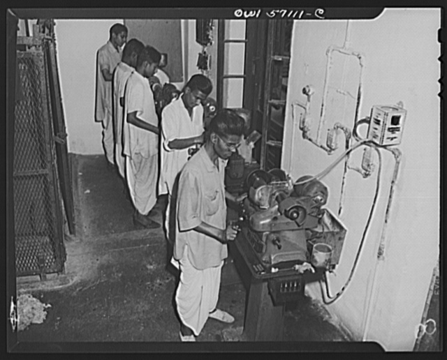 """United States """"lend-lease"""" program in eastern India. These machines are ordinary Black and Decker valve facers, commonly seen in American gargaes. Supplied to India under lend-lease, they are used for sights and binouculars"""