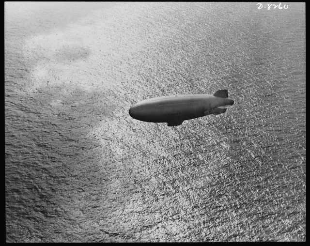 U.S. Navy starts out on patrol duty. Soaring over the Atlantic Ocean, a U.S. Navy blimp is silhouetted against the sparkle of waves. These lighter-than-air craft are used for anti-submarine patrols