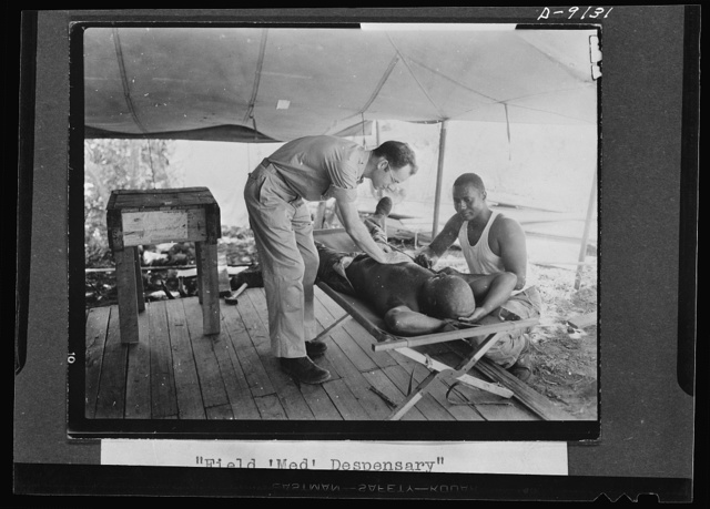 """U.S. Negro troops in New Guinea. Medical care is well provided for all American and allied forces in New Guinea. Here a field medical dispensary is set up and operated by a Negro medical detachment. Soldiers go daily for """"sick calls"""" and any possible illness is checked or given immediate care"""
