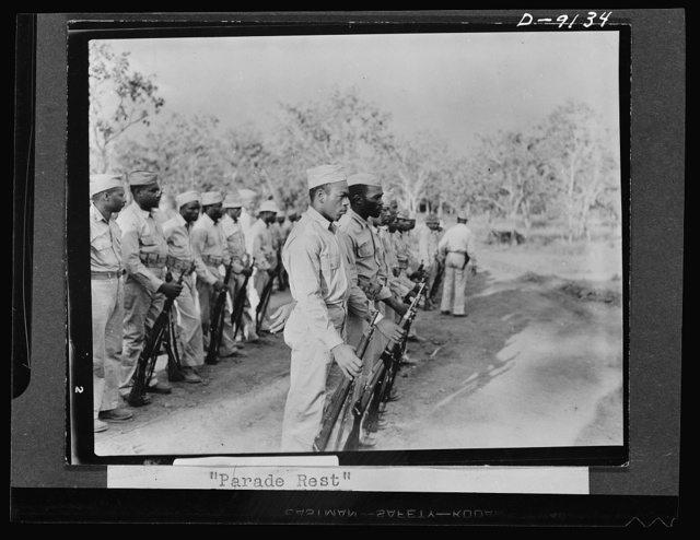 "U.S. Negro troops in New Guinea. ""Parade rest"" command is given to soldiers holding ""retreat"" formation in New Guinea. Apparently third soldier is rear rank failed to hear command"