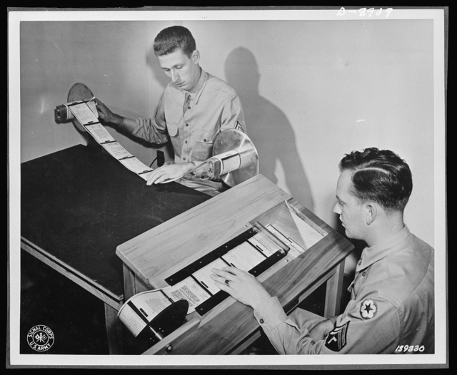 """V-mail. Paper reproduction for V-mail microfilm are inspected and then cut into individual letters by the """"chopper"""" at the Pentagon building, Washington, D.C. V-mail is available to and from the armed forces stationed outside the United States. It is only 1/65th the weight of ordinary mail and saves ninety-eight percent of the cargo space required for ordinary letters. 1,600 letters can be placed on a roll of film little larger than a pack of cigarettes"""