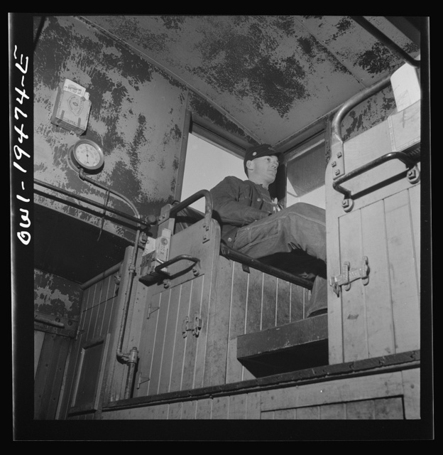 Walter V. Dew, rear brakeman, on the Atchison, Topeka, and Santa Fe Railroad between Chicago and Chillicothe, Illinois, watching the train from the cupola