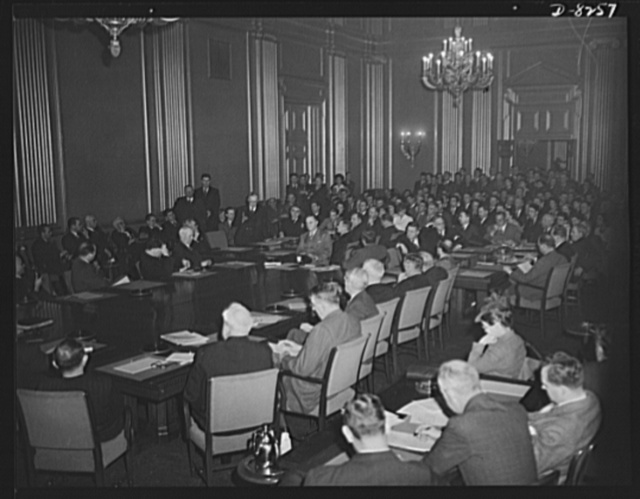 War Labor Board anthracite hearing. Labor members, seated at the left of conference table, and employer members, seated at the right, hear testimony of striking coal miners at the hearing on the anthracite strike before the National War Labor Board, January 15, 1943
