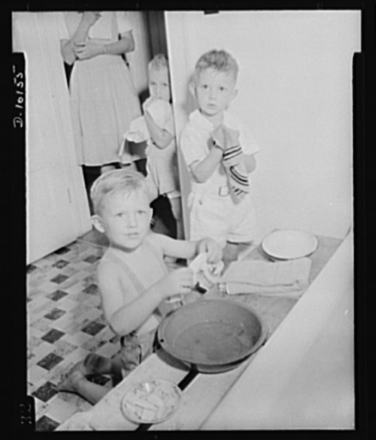 """War nursery schools. Virgina. """"Let's get this over so we can eat,"""" appears to be the thought uppermost in the minds of Bobby Marlatt and Eddie Cord as they gingerly go about the process of cleaning up at a Virginia war nursery. The nursery is conducted for war workers' children at a nearby ordnance plant"""