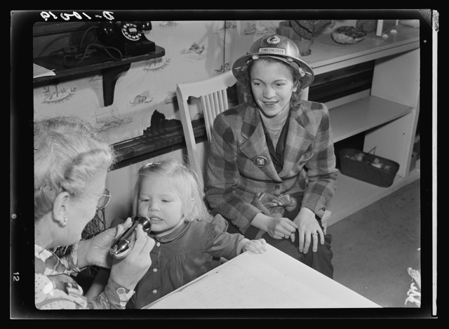 War workers' nursery. The morning checkup at modern nursery schools includes mouth and throat inspection. Mrs. Arlene Corbin, time checker at a Richmond, California shipyard waits until two-and-a-half-year-old Arlene is pronounced in perfect health by Mrs. Elsie Curran, supervisor at the Bella Vista Nursery in Oakland, California