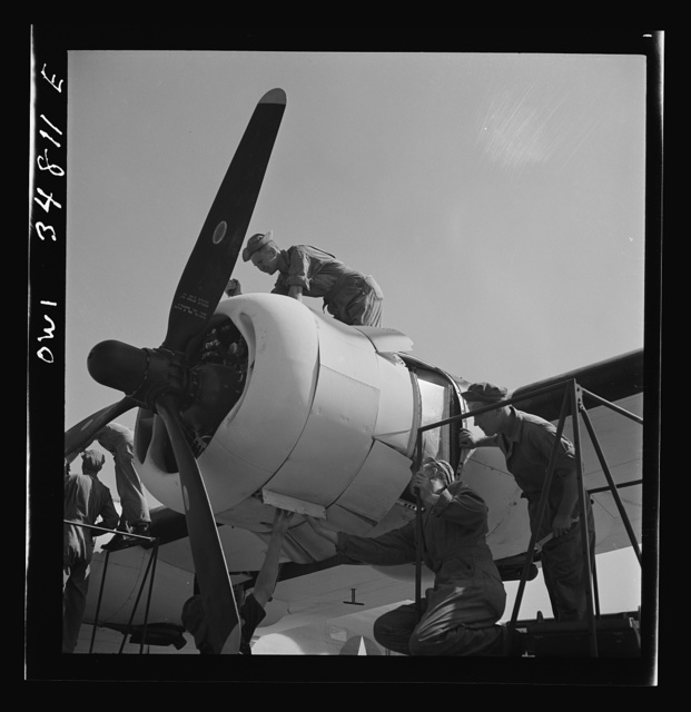 Warner Robins, Georgia. Air Service Command, Robins Field. Mechanics of an air depot group removing the cowling of one of the engines of a B-24 Liberator bomber
