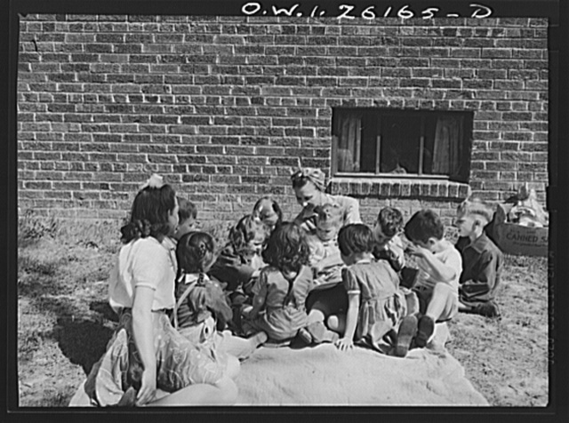 Washington, D.C. A day nursery for pre-school children of mothers engaged in war work, operated under the supervision of the District of Columbia Health Department by Mrs. Leroy Bonbrest at her home at 1144 Branch Avenue, S.E. Mrs. Bonbrest and the children out in the yard looking at a picture book