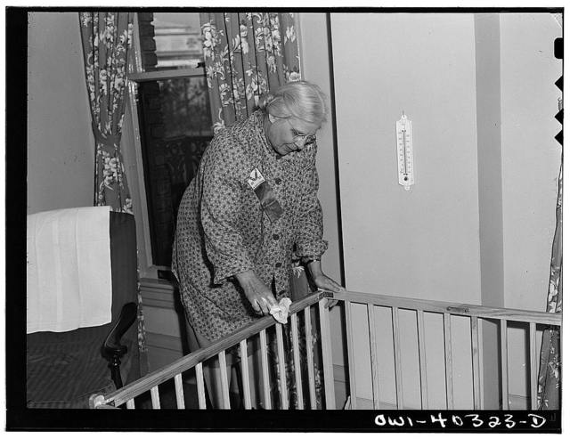 Washington, D.C. A volunteer worker in the nursery at the United Nations service center cleaning a children's playpen for the next occupant