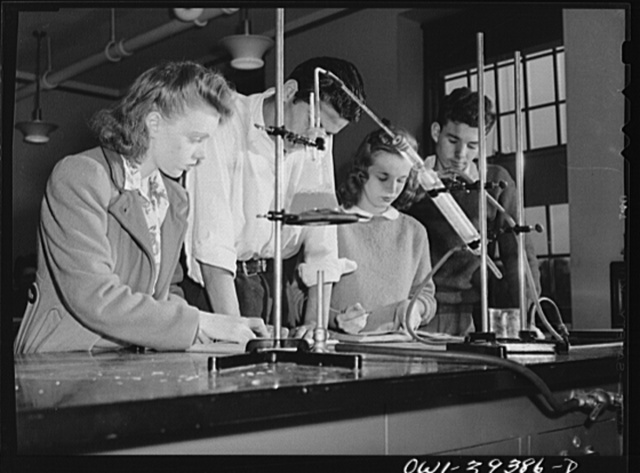 Washington, D.C. Chemistry students making notes in the apparatus used for an experiment at Woodrow Wilson High School