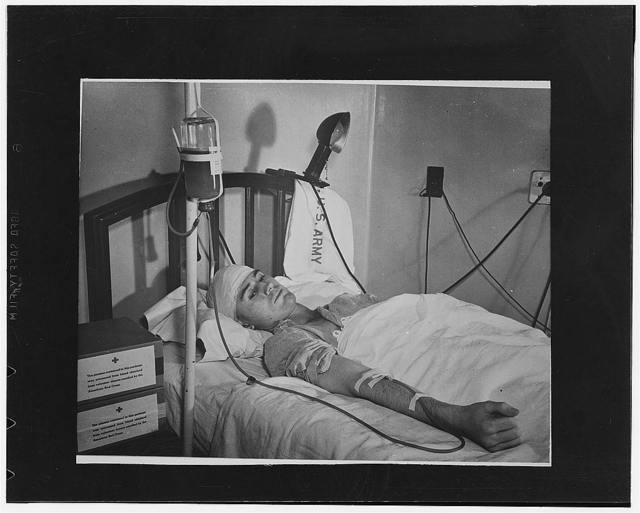 Washington, D.C. First Lieutenant Landis D. Morris, of Olar, South Carolina, wounded by a sniper's bullet at Safe, receiving a transfusion of blood plasma at Walter Reed Hospital