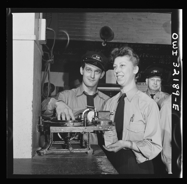 Washington, D.C. Frances Lewis, a streetcar conductor for the Captiol Transit Company, counting tokens on a machine at the end of the day