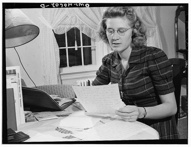 Washington, D.C. Lynn Massman, wife of a second class petty officer who is studying in Washington, writing letters while her baby is having his afternoon nap