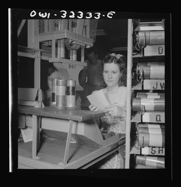 Washington, D.C. Mrs. Eva Poovey working with pneumatic tubes from which telegrams are taken at the Western Union telegraph office