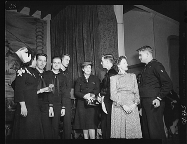 Washington, D.C. Mrs. James M. Landis, Mrs. James Forrestal, center, with the enlisted personnel of the Navy School of Music, who performed at the kitchen shower of the Walsh Club for war workers, and other artists who contributed their talent. Left to right: Mrs. Virginia Varney, singer; Thomas Parker, Dale McConnell, Golden Smith, Mrs. James Forrestal, Frank Gambel, Mrs. John Leavell, concert pianist, and Neil Darnell