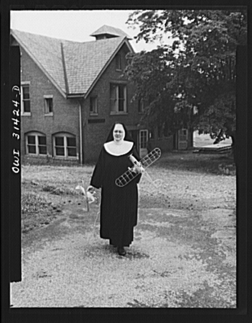 "Washington, D.C. Sister Aquinas, ""flying nun"", with model planes in hands walking toward the aeronautics laboratory at Catholic University where she gives a daily three-hour preflight Civil Aeronautics Authority course for instructors"