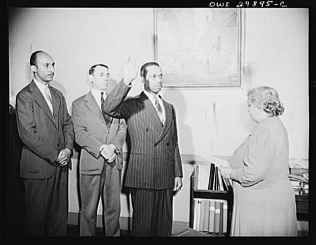 Washington, D.C. The distinction of being the first Negro to become a member of the Trial Bureau of the Department of Justice goes to Martin A. Martin of Danville, Virginia, who was sworn in on May 31, 1943. Mrs. Nellie G. Plumley, appointment clerk, is administering the oath. In the background is Attorney Oliver Hill of Richmond, Virginia and Frank Coleman, Special Assistant to Attorney-General Biddle. Mr. Martin also has the rank of Special Assistant