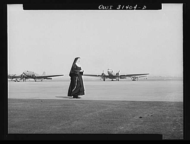 """Washington, D.C. The """"flying nun"""" from Ironwood, Michigan, walking down the field at the Washington National Airport after taking her class through the hangars. Sister Aquinas holds a student pilot's license and has many flying hours to her credit"""