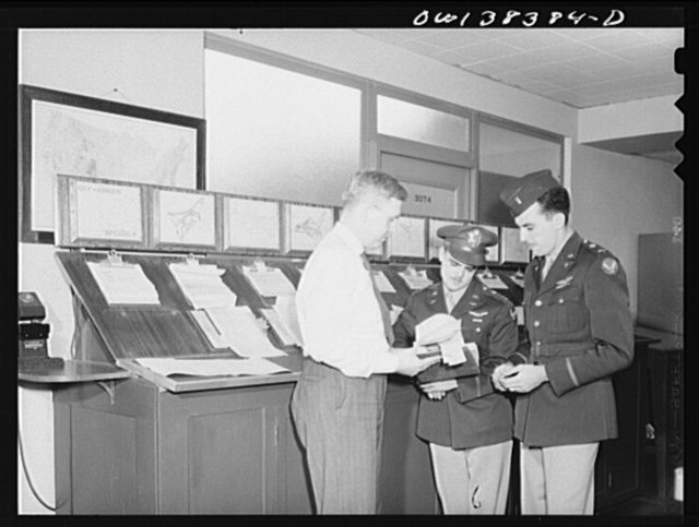 Washington, D.C. The U.S. Weather Bureau station at the National Airport. Weather information is essential to all aircraft pilots. Here the forecaster is shown discussing the type of weather the pilots may encounter on their proposed flights