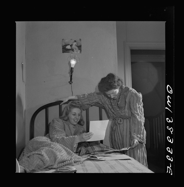 Washington, D.C. Two girls looking at pictures in their room in a boardinghouse