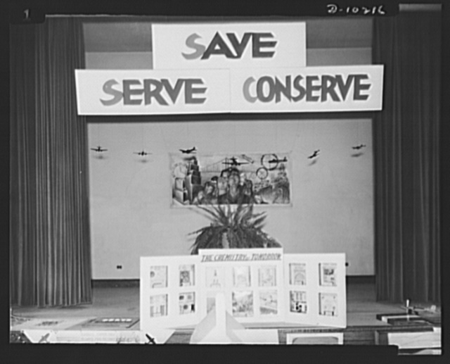 "Washington public schools go to war. The public schools of Washington, D.C., like those in most other sections of the country, have revised their curricula to fit the pupils for fuller participation in the war effort. At a recent exhibit of work done in the Negro schools under the Office of Civilian Defense, the slogan, ""Save, Serve, Conserve"" was prominently displayed. Photo shows this slogan adorning an exhibit by one of the chemistry classes"