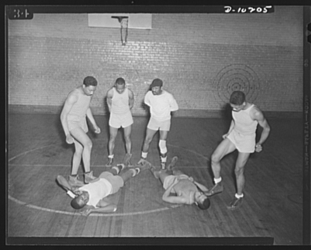 Washington public schools go to war. The public schools of Washington, D.C., like those in most other sections of the country, have revised their curricula to fit the pupils for fuller participation in the war effort. Physical fitness is now an important part of this new program. Photo shows high school boys in gym illustrating a phase of their toughening-up exercises