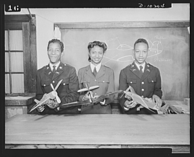 Washington public schools go to war. The public schools of Washington, D.C., like those in most other sections of the country, have revised their curricula to fit the pupils for fuller participation in the war effort. They have gone all-out for the Program of Civilian Defense. Photo shows pupils from model airplane class demonstrating types of fighter planes