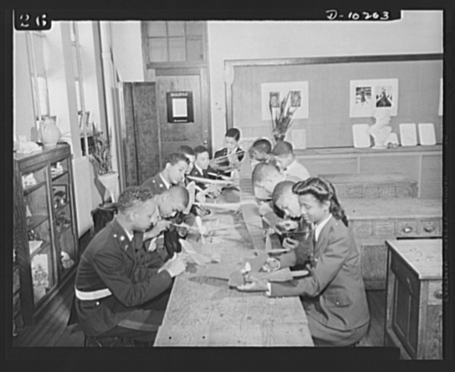 Washington public schools go to war. The public schools of Washington, D.C., like those in most other sections of the country, have revised their curricula to fit the pupils for fuller participation in the war effort. They have gone all-out for the Program of Civilian Defense. Photo shows class in model airplane construction at Phelps Vocational High School