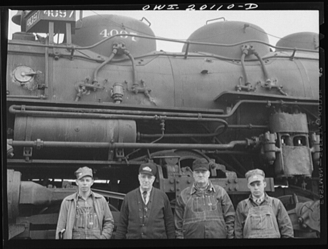 Wellington, Kansas. An Atchison, Topeka and Santa Fe Railroad crew posing in front of their engine before pulling out of Wellington for Waynoka, Oklahoma. Left to right: D.C. Quivey, head brakeman; D.B. Wallingford, conductor; B.F. Hale, engineer; and fireman Walker