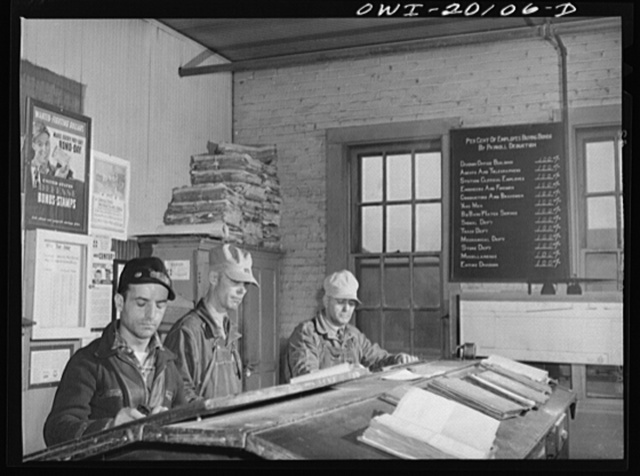Wellington, Kansas. Atchison, Topeka and Santa Fe engine crew checking in after a day's run. Left to right: brakeman W.I. Pace; fireman Edward L. Hicks; and engineer J.B. Aubuchon. Note blackboard showing participation of railroad men in war ond campaign
