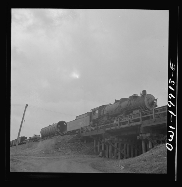 Wellington, Kansas. Train about to leave for the West coast from the Atchison, Topeka and Santa Fe Railroad yards, carrying a huge naval gun and giant metal cylinder for the Kaiser steel mill in California