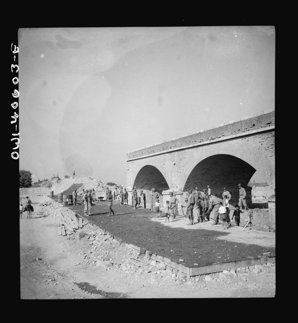 When the Germans fled Sicily they dynamited every bridge and road juction they had time to. But Allied army engineers and Sicilian workers are repairing the arteries so that normal traffic may flow once again over the island