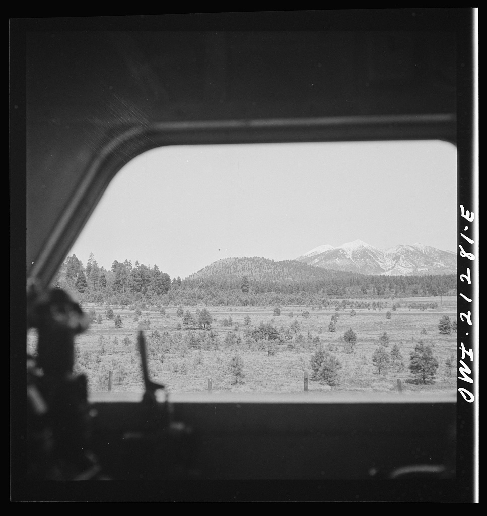 Williams (vicinity), Arizona. The San Francisco peaks, in the Sierra Nevada range, near the California border, seen through the engineer's window of a diesel freight locomotive on the Atchison, Topeka and Santa Fe Railroad between Winslow and Seligman, Arizona
