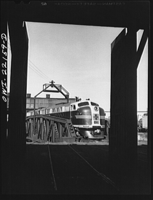 Winslow, Arizona. Atchison, Topeka, and Santa Fe Railroad diesel freight engine coming out of the roundhouse. The entire engine consists of four units, only two of which can be accomodated in a stall at the roundhouse or on the turntable